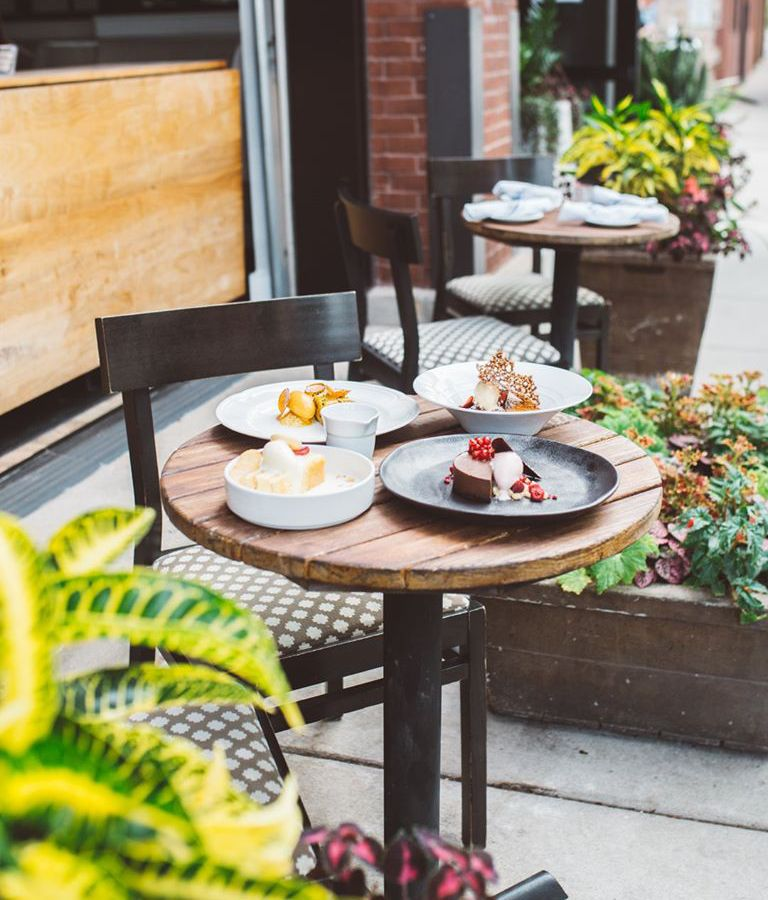 Two bistro tables outside Spoon and Stable