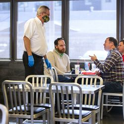 Longtime Hires Big H employee Jim Merrill talks with customers Brian Davis, Jesse Whitchurch and Rick Pike as he works his last week of shifts at the burger joint in Salt Lake City on Friday, Jan. 8, 2021. Merrill has worked at the company for 52 years.