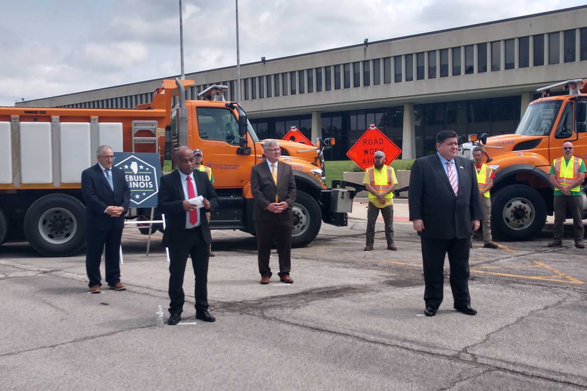 Gov. J.B. Pritzker, right, and other state officials at a news conference in Springfield on Wednesday.