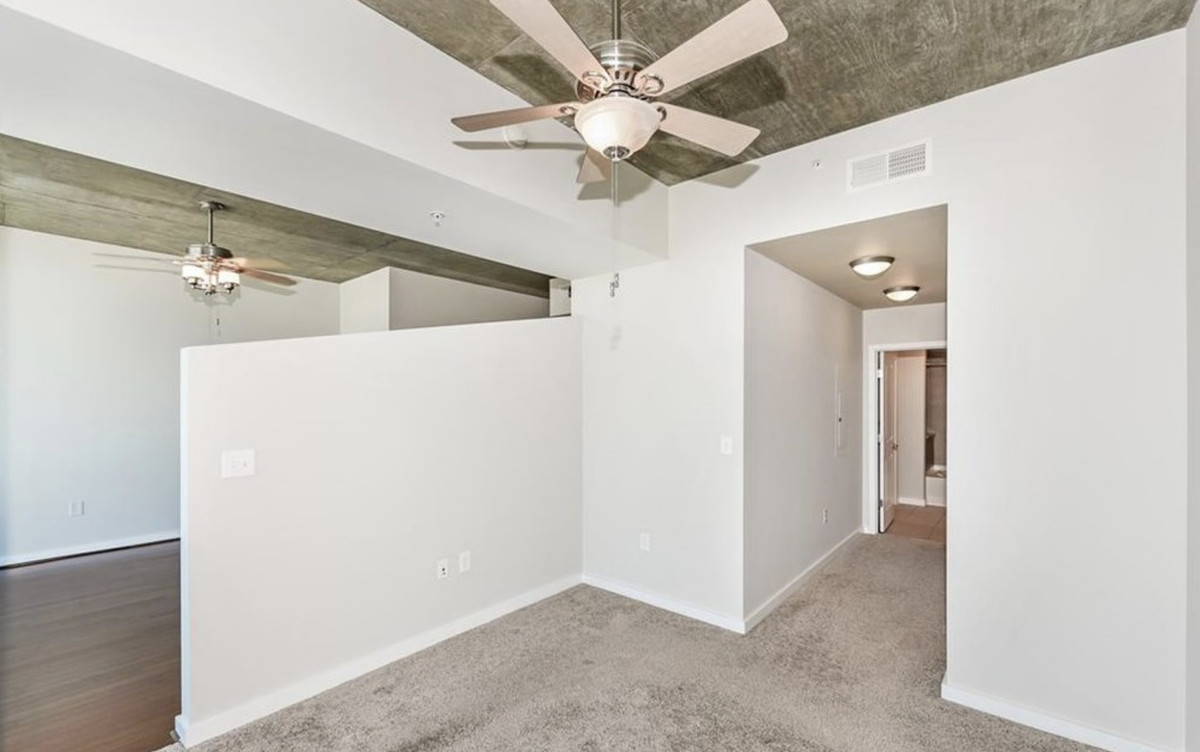 Empty bedroom with gray carpet, ceiling fan and short hallway to the bathroom.