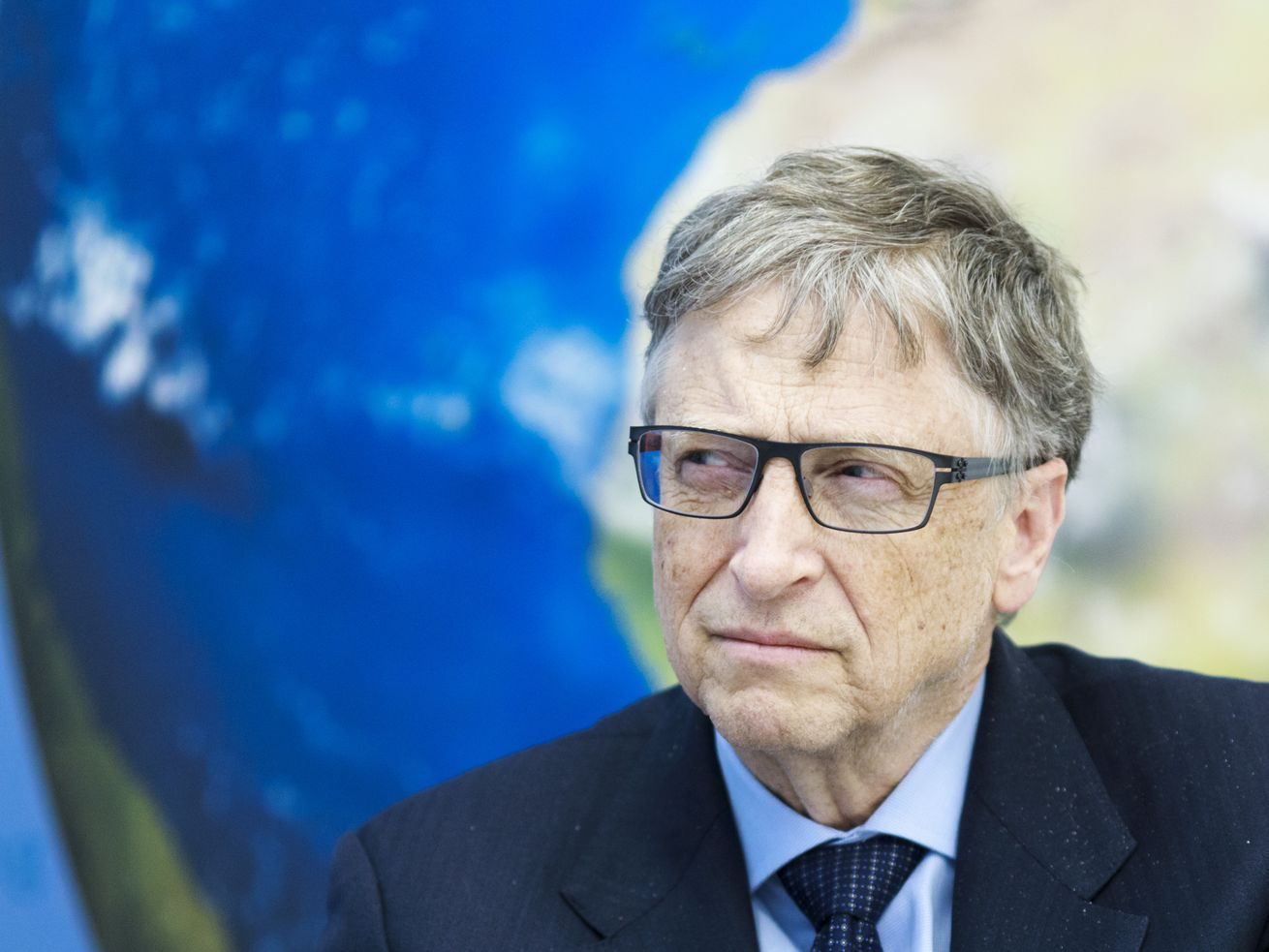 Bill Gates squints while sitting in front of a picture of Earth.