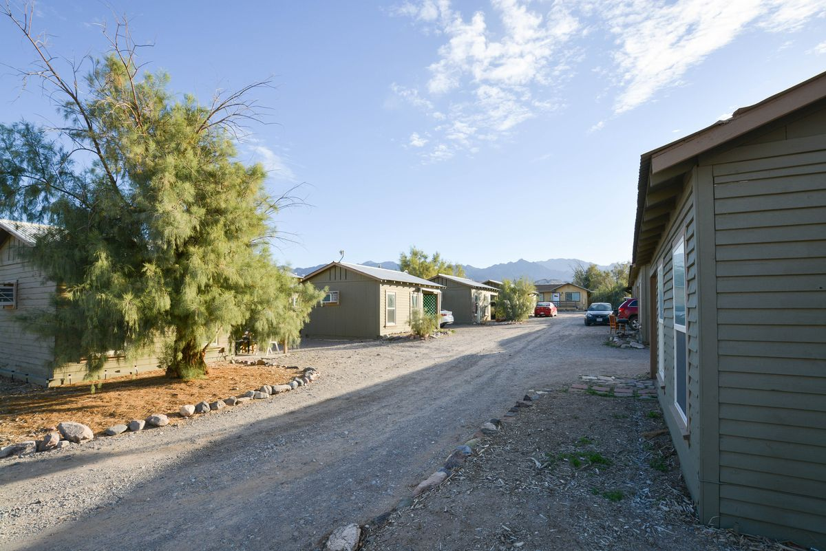 A wash of small houses on dusty streets behind a public desert property.