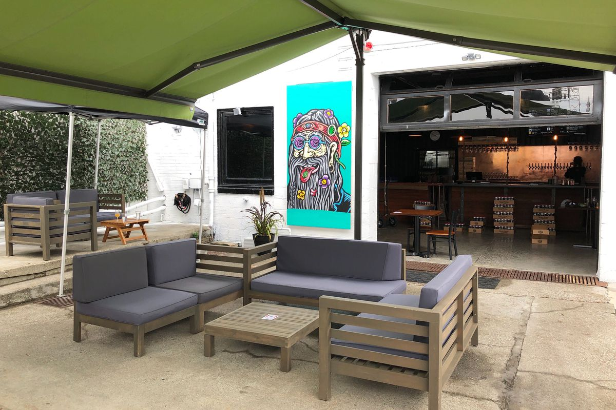 The outdoor patio at Great Notion, with tables, chairs, a green overhanging tent, and a painting of an old, bearded hippie in the background