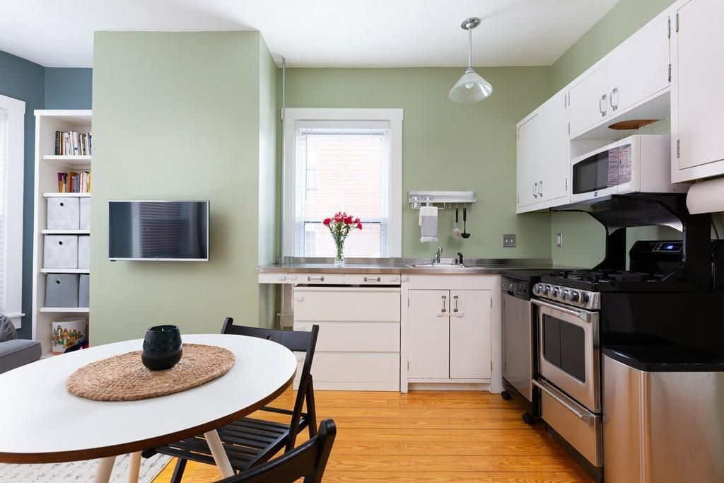 The same living room-kitchen area, but a closeup on the kitchen, with a table and chairs in the foreground.