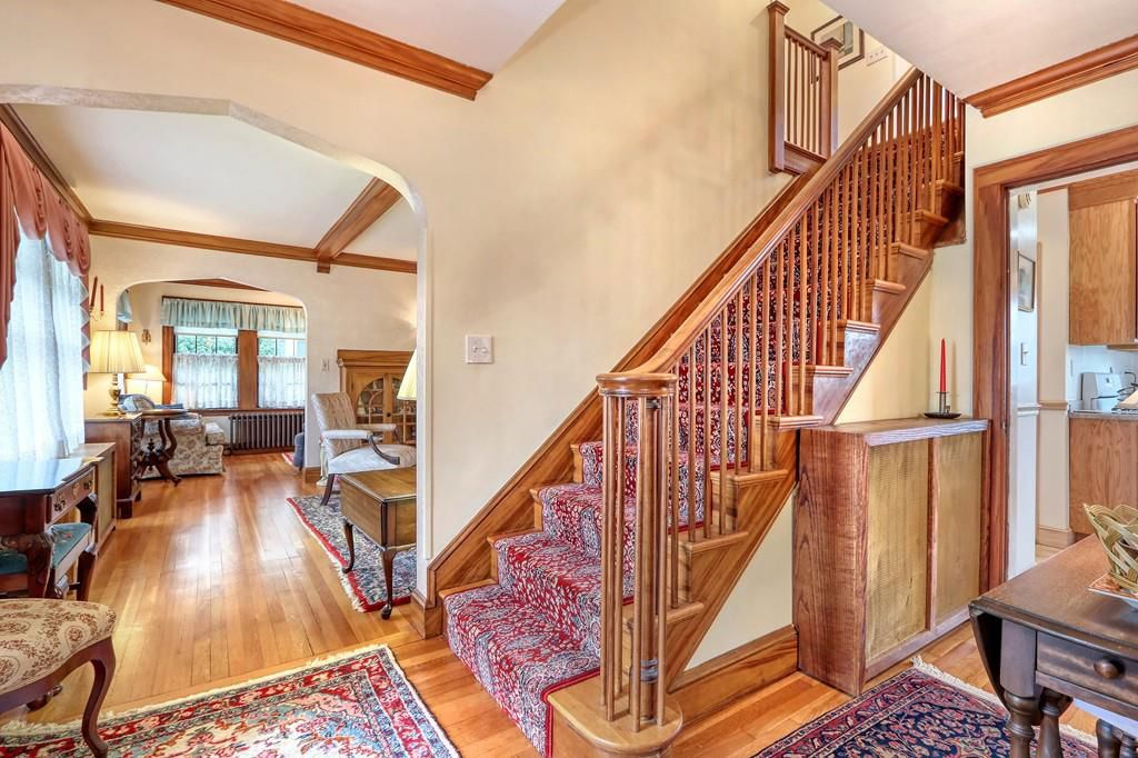 An entry foyer with a wood-bannister staircase and a large opening to a living room with furniture.