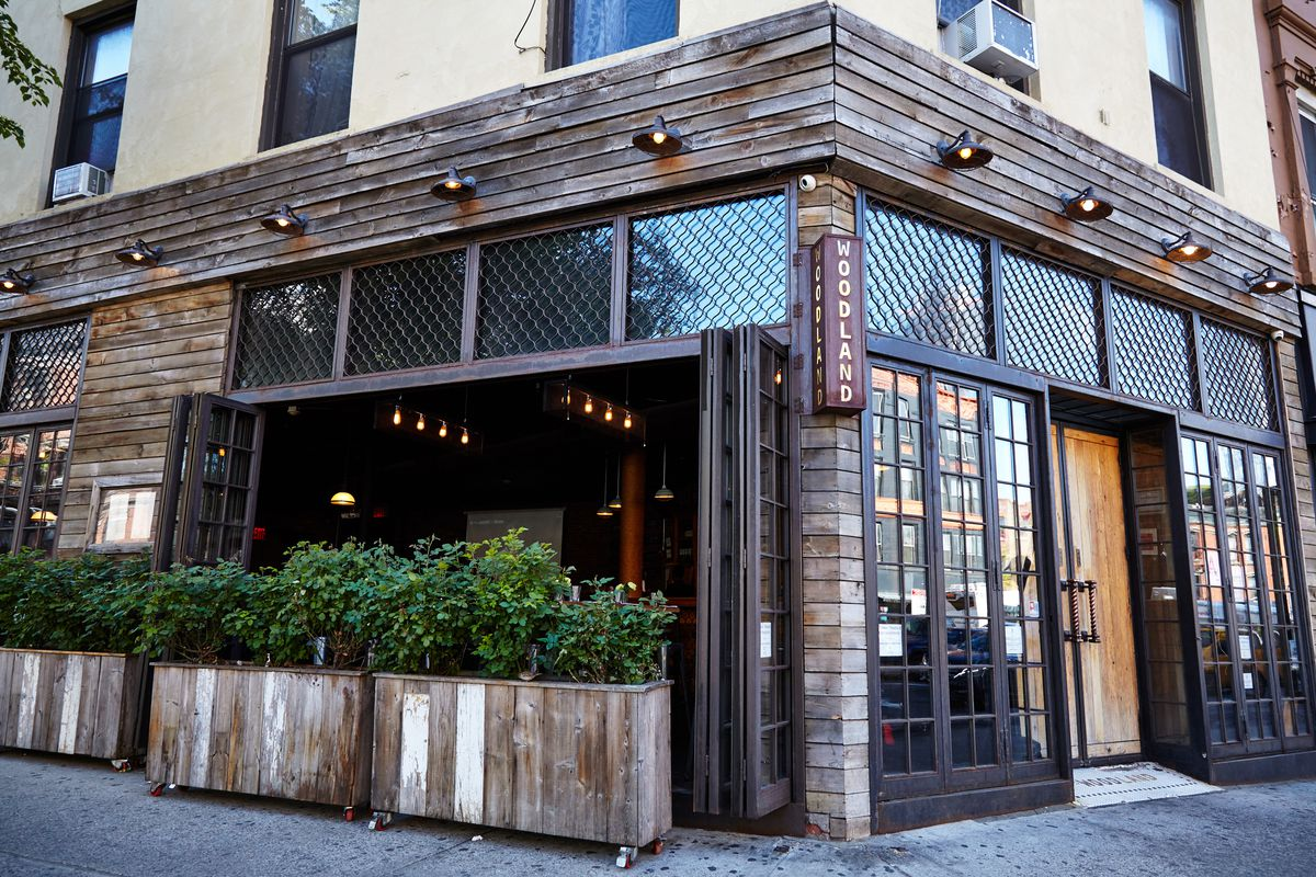 The exterior of woodland bar in park slope shows dark wooden frames, large glass windows and doors, and planters