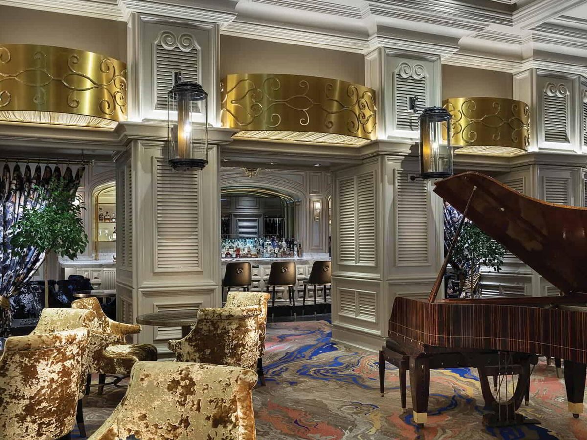 A lounge with a baby grand piano on the right.