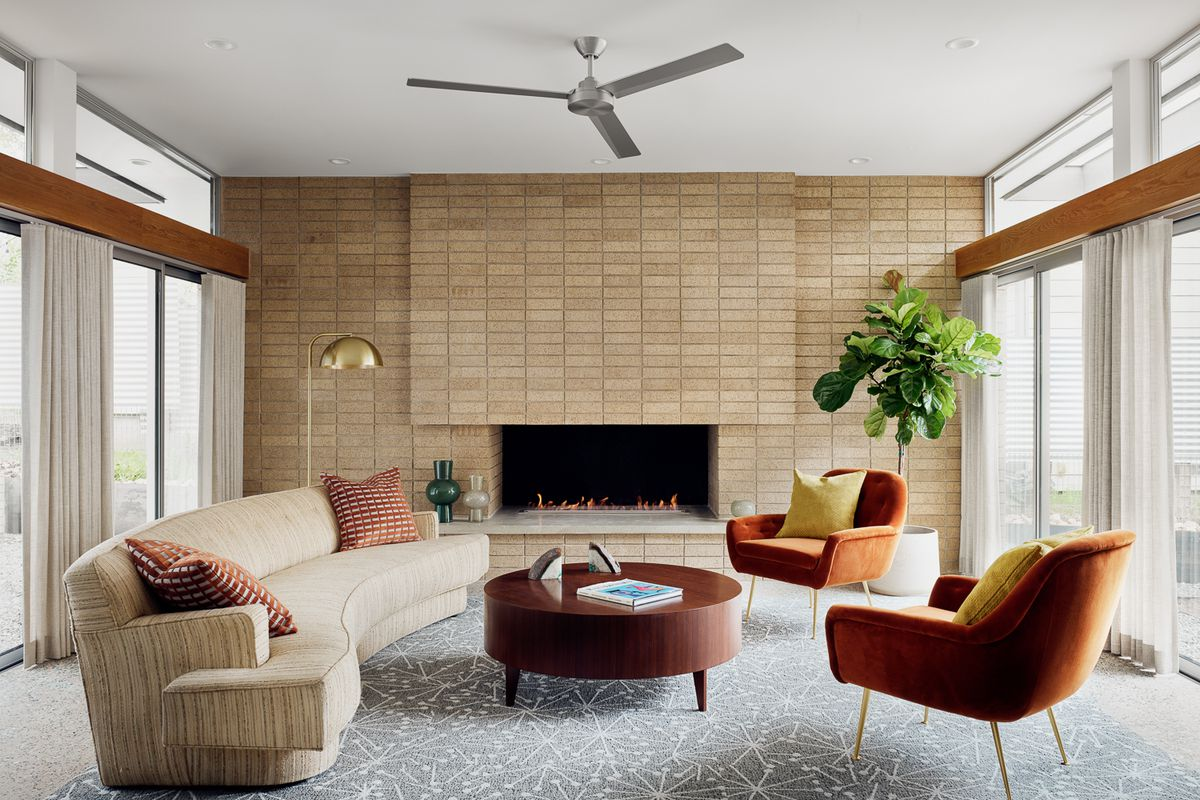Photo of living room featuring brick fireplace and midcentury furniture.