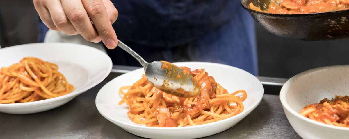 Pasta being plated for A Mano