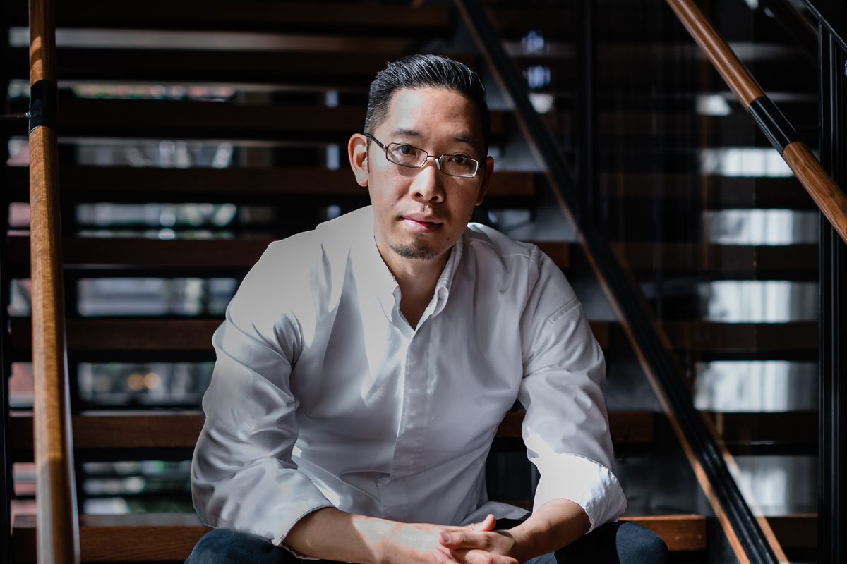 A portrait shot of an Asian-American chef in a white coat sitting on a flight of stairs.
