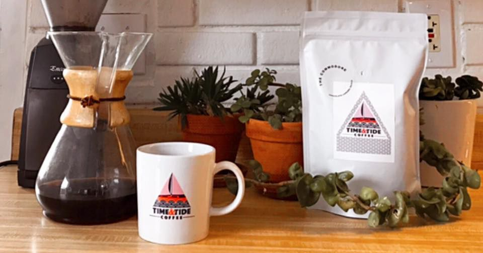 Chemex coffee, mug, and coffee bag on wooden counter in front of white tile backsplash
