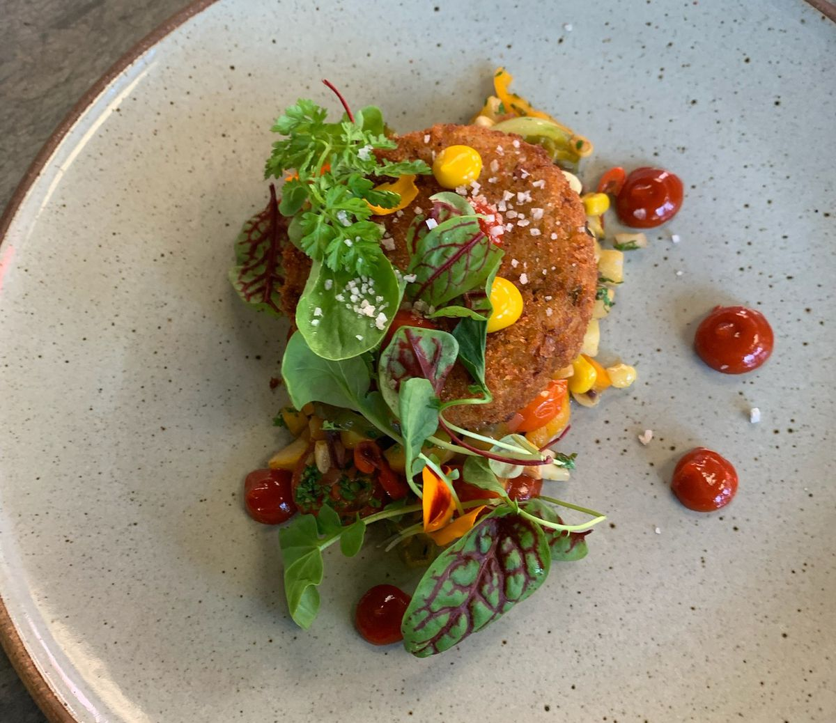 A breaded crab croquette garnished with green herbs sits on a bed of corn on a gray plate.