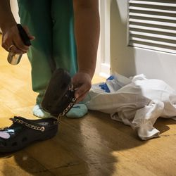 Nurse practitioner Capri Reese cleans her Crocs with antibacterial spray, then puts her scrubs in the washing machine and immediately showers at her South Loop apartment after a 12-hour shift at Roseland Community Hospital, where three patients suffering from COVID-19 died, Tuesday afternoon, April 28, 2020.