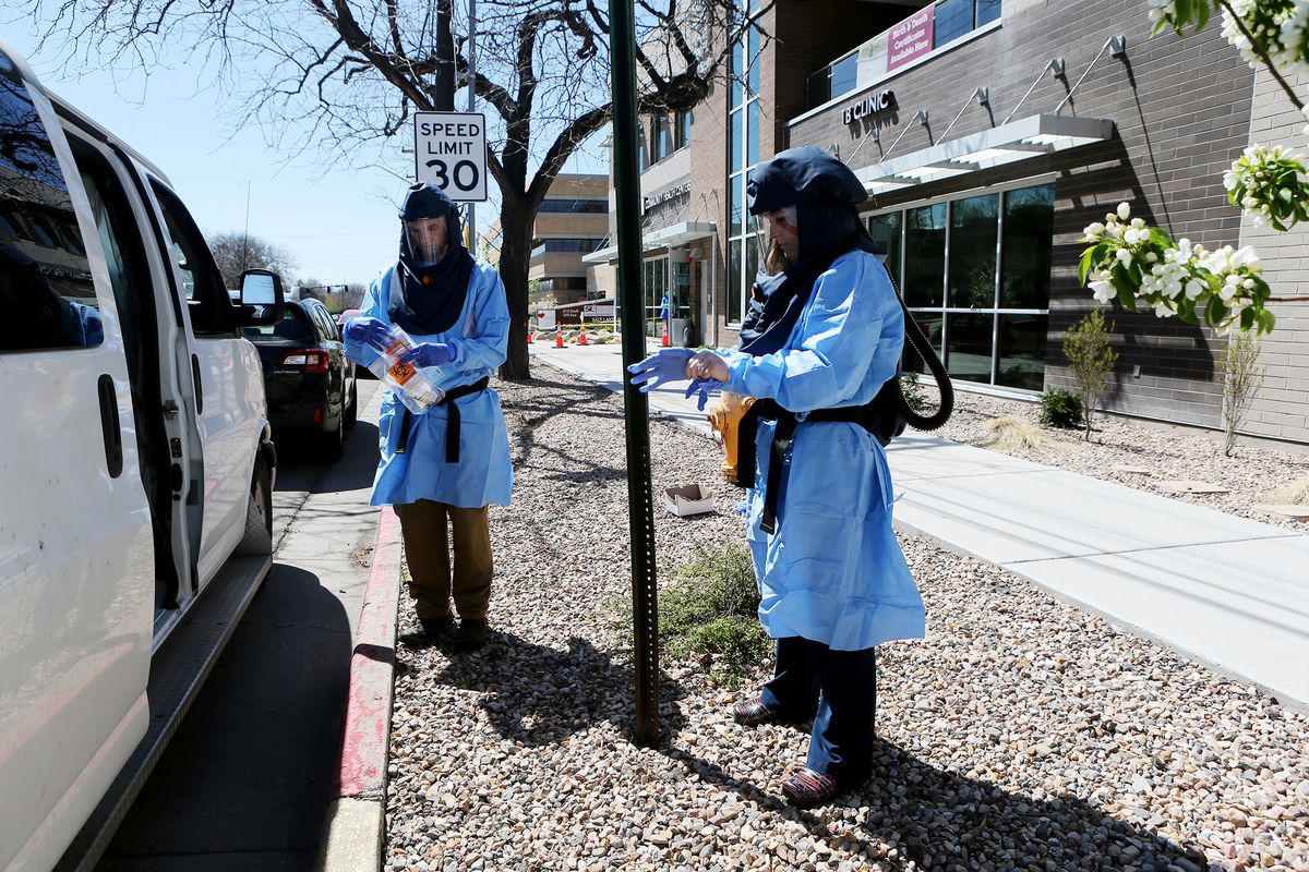 Travis K. Langston, left, and Lee Cherie Booth, both nurses with the Salt Lake County Health Department, test an individual for COVID-19 outside of the Salt Lake City Public Health Center on Friday, April 10, 2020.