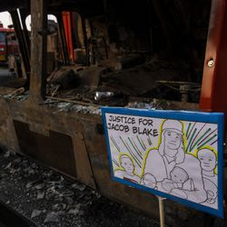 A Justice for Jacob Blake sign sits in front of a burned out Garbage Truck, during a protest over the shooting of Jacob Blake, Tuesday, Aug. 25, 2020, in Kenosha, Wis.