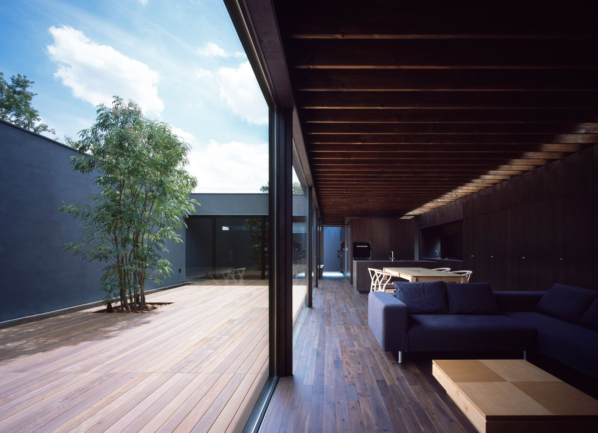 An airy open living room and kitchen with a coffee table, sofa, and dining able, opens to a courtyard, where there is a tree.