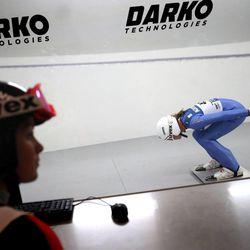Women's Ski Jumping USA team member Alissa Johnson holds an in-run position inside a wind tunnel built by Layne Christensen, founder of Darko Technologies, in Ogden's Business Depot on Thursday, Sept. 26, 2013.