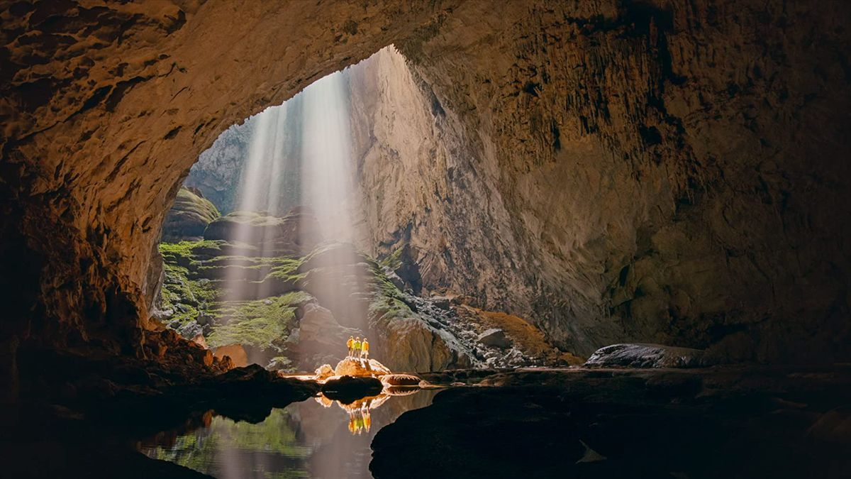 Four people stand in a cave, and the sunshine spreads through the door