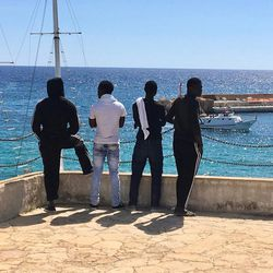 Having landed on the Italian island of Lampedusa, four young male refugees look over the Mediterranean Sea waters they had traversed — and survived — only days earlier.