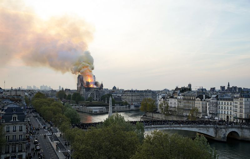 A shot of central Paris shows flames and smoke billowing from the roof at Notre Dame Cathedral.
