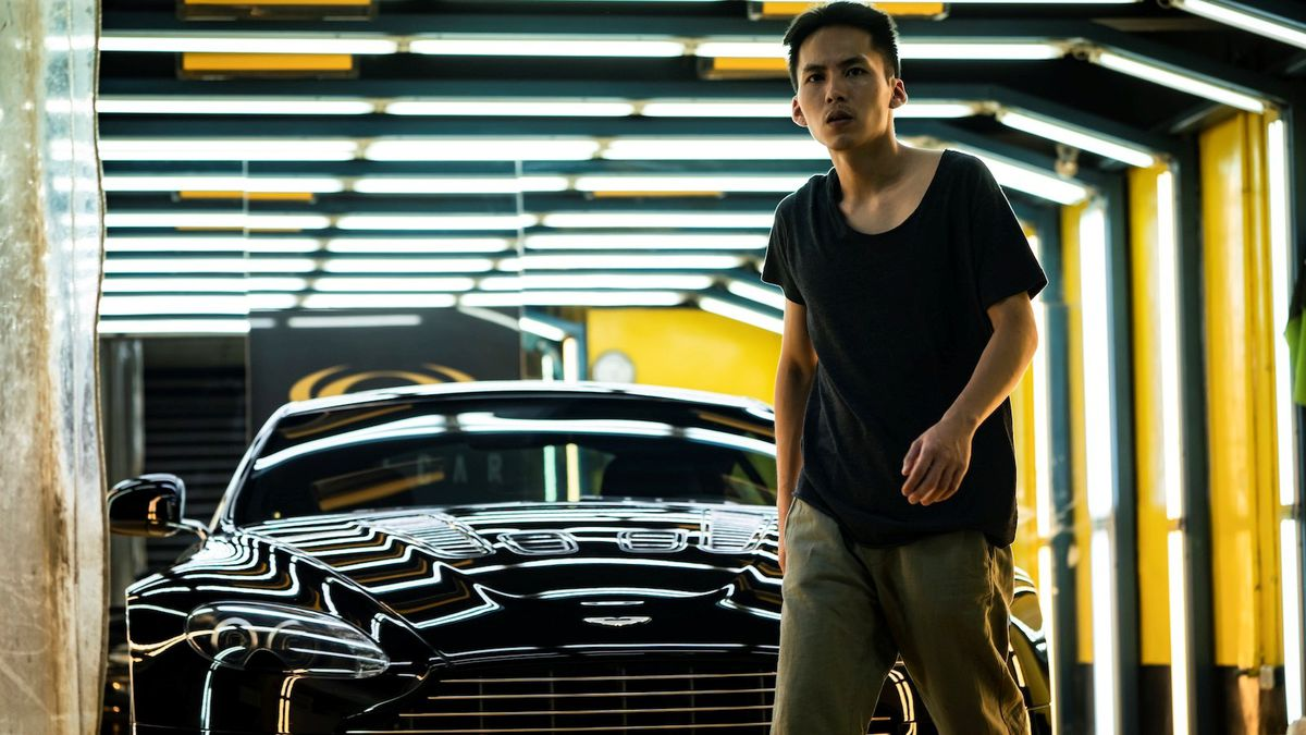 A Sun: a man stands in front of a sports car with light glistening on the hood