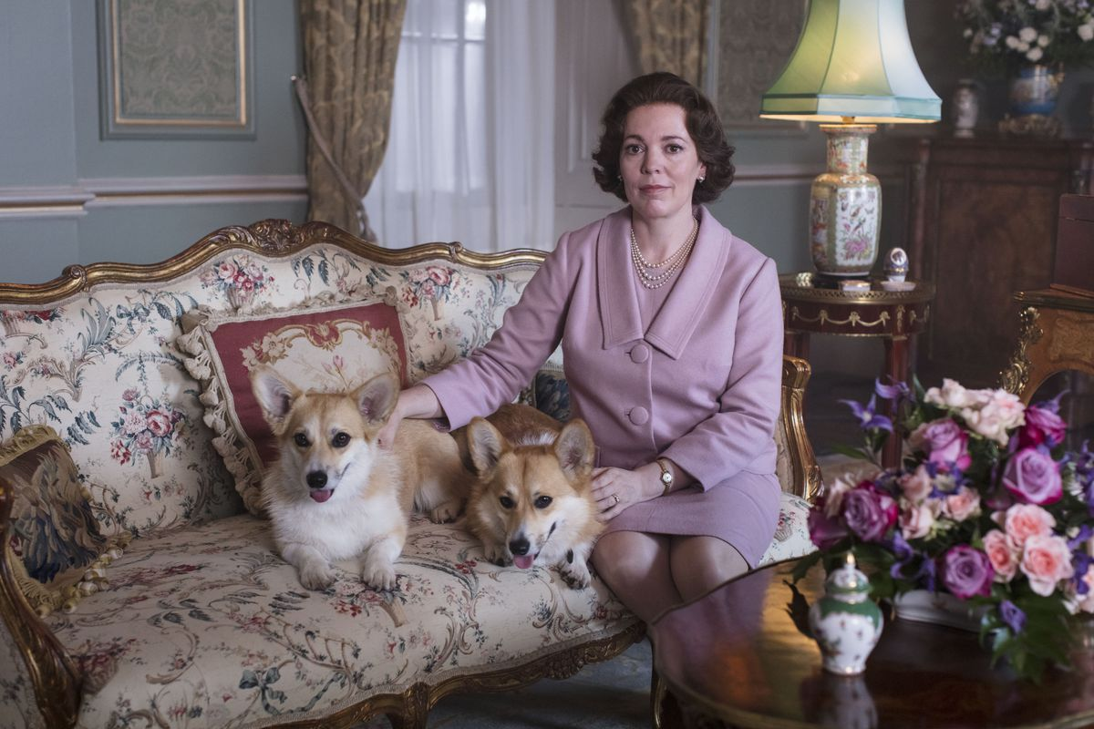 olivia colman as queen elizabeth, sitting in a pink suit with two corgis