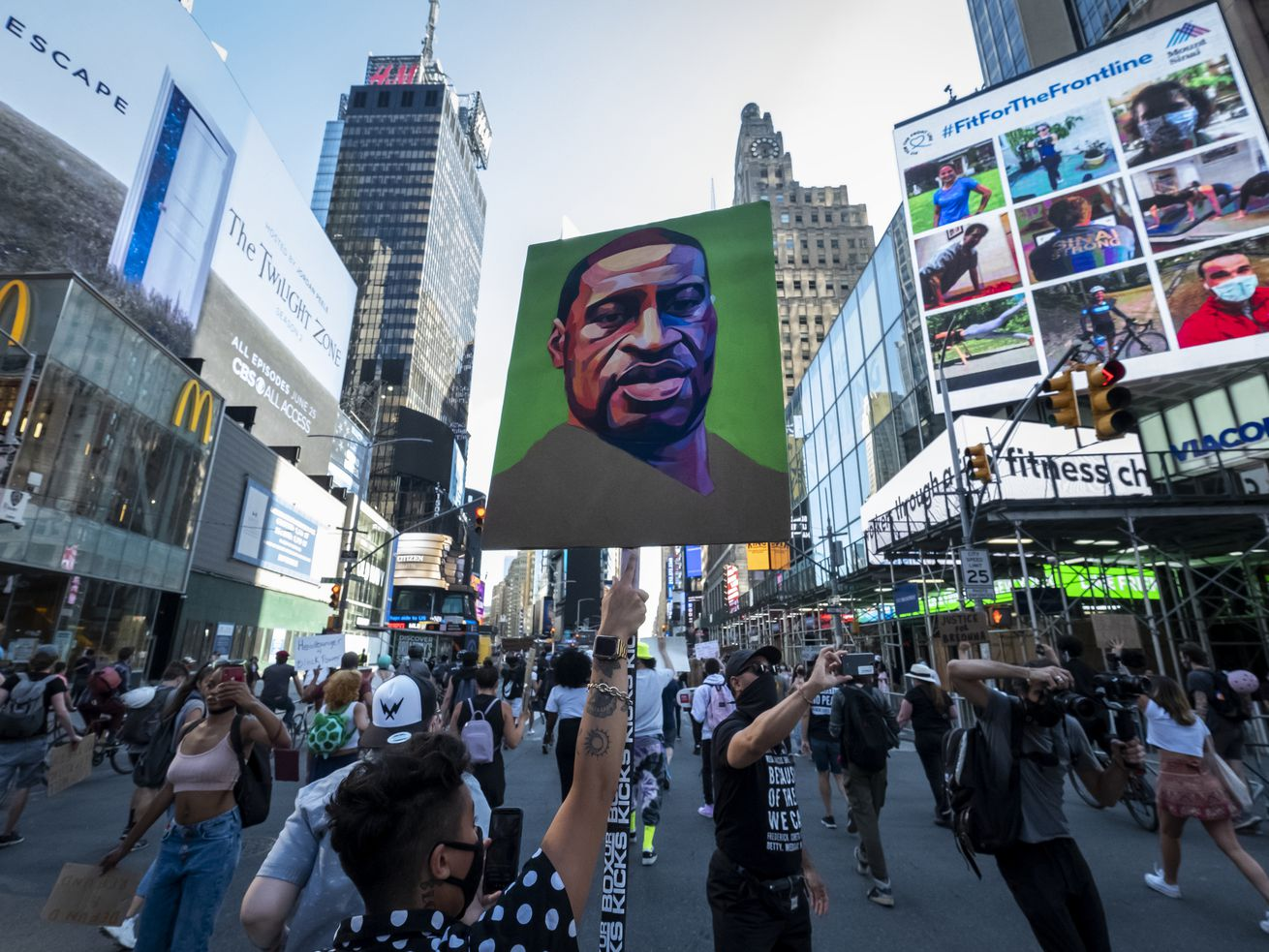 "Protesters wearing masks walk through the streets of Times Square holding up their hands and chanting, ""Hands Up Don't Shoot"" after police officers conceded to let protesters that are trying to peacefully march through Times Square with one protester holding a sign with a portrait painting of George Floyd."