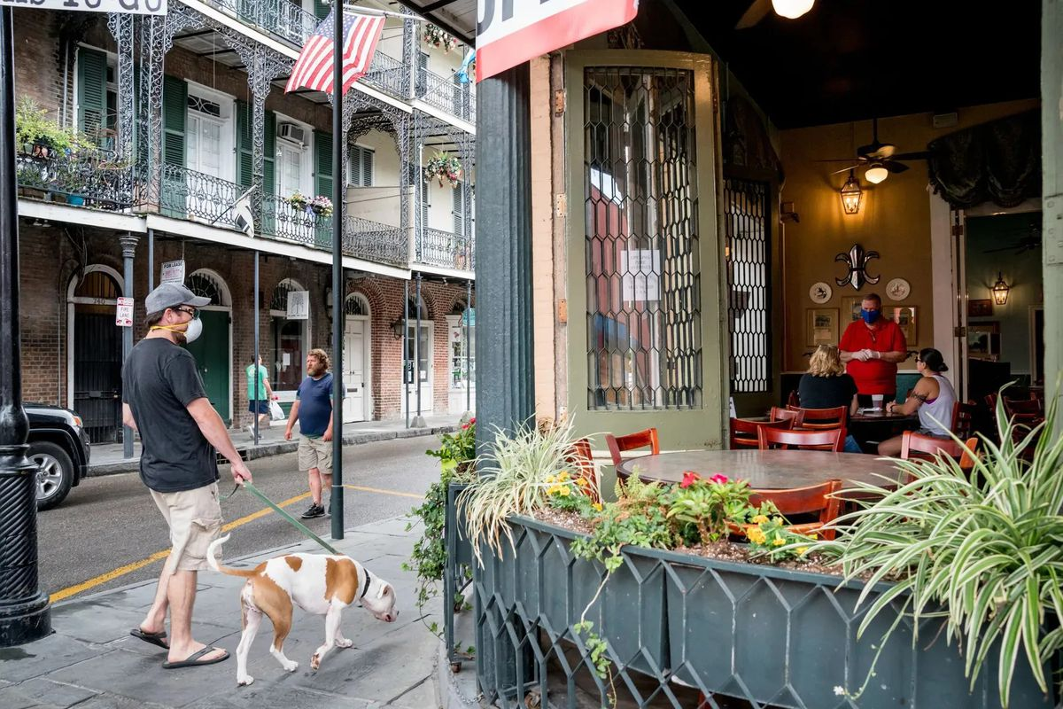 Masked man walks his dog down a French Quarter street