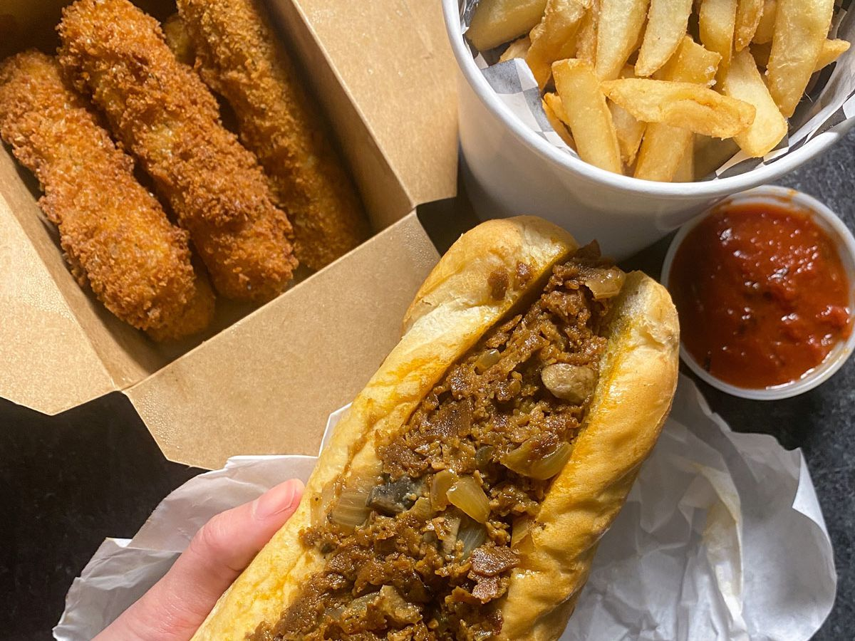 A photo of a vegan Philly cheesesteak, mozzarella sticks, and fries from Buddy's Steaks