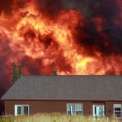 A wildfire burns near a home Sunday, Sept. 9, 2012 on Casper Mountain in Casper, Wyo. Residences and campgrounds were evacuated as the uncontained wildfire spread across the southeast portion of the mountain.