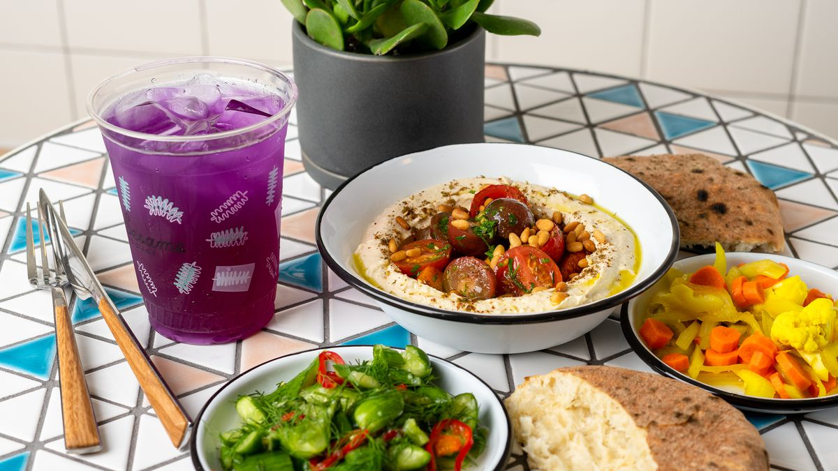 A hummus bowl from Little Sesame is flanked by juice, salad, pita bread, and pickled vegetables