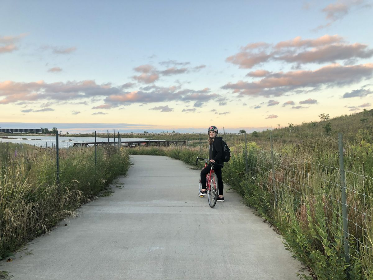 A wide concrete path with tall grass on either side. A biker in the distance is stopped gazing at the clouds at dusk.