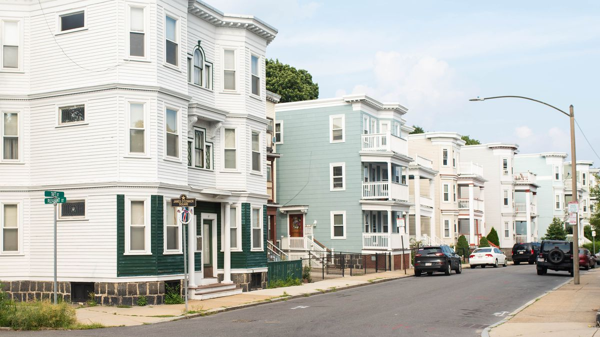 A row of three-story apartment buildings along a mostly empty street.