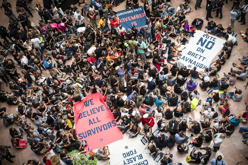 """Sit-in protesters against the nomination of Brett Kavanaugh to the Supreme Court in the Court atrium holding signs that read, """"Vote no on Brett Kavanaugh,"""" and, """"We believe all survivors."""""""