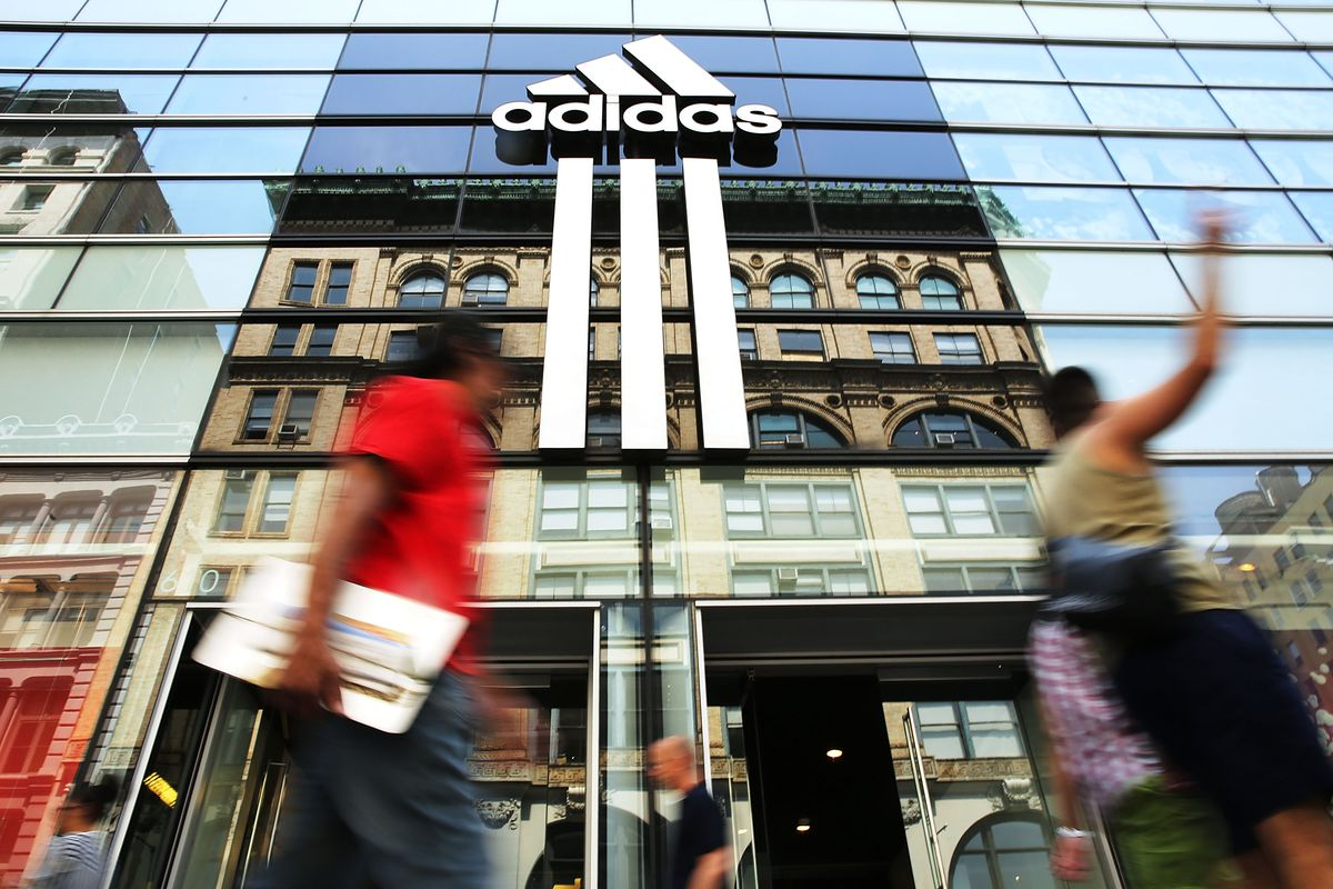 People walk past a shiny Adidas store in New York City.
