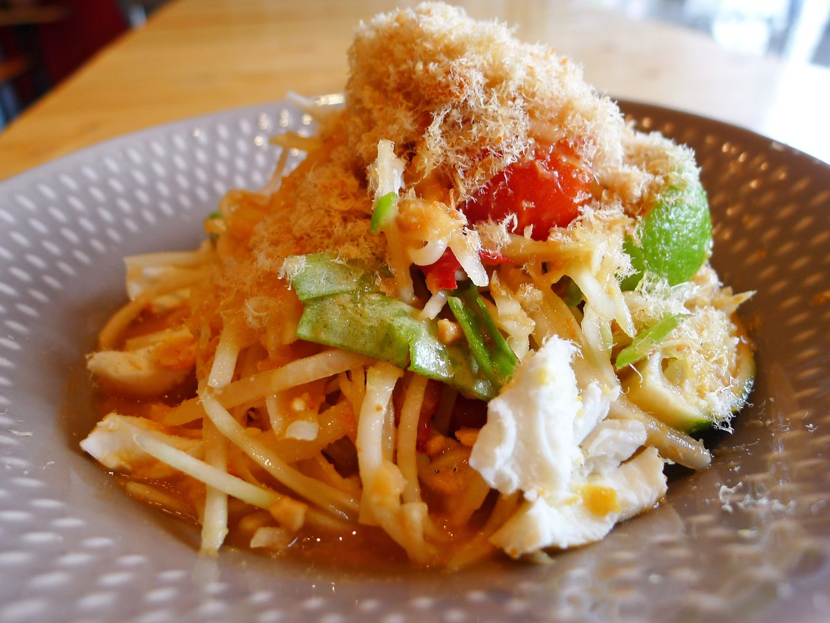 A heap of shredded green papaya with a haystack of dried fish shavings on top.
