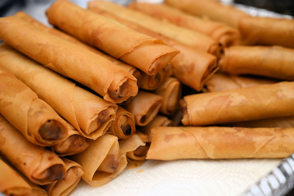 A stock photo of a plate stacked with rows of crispy lumpia.
