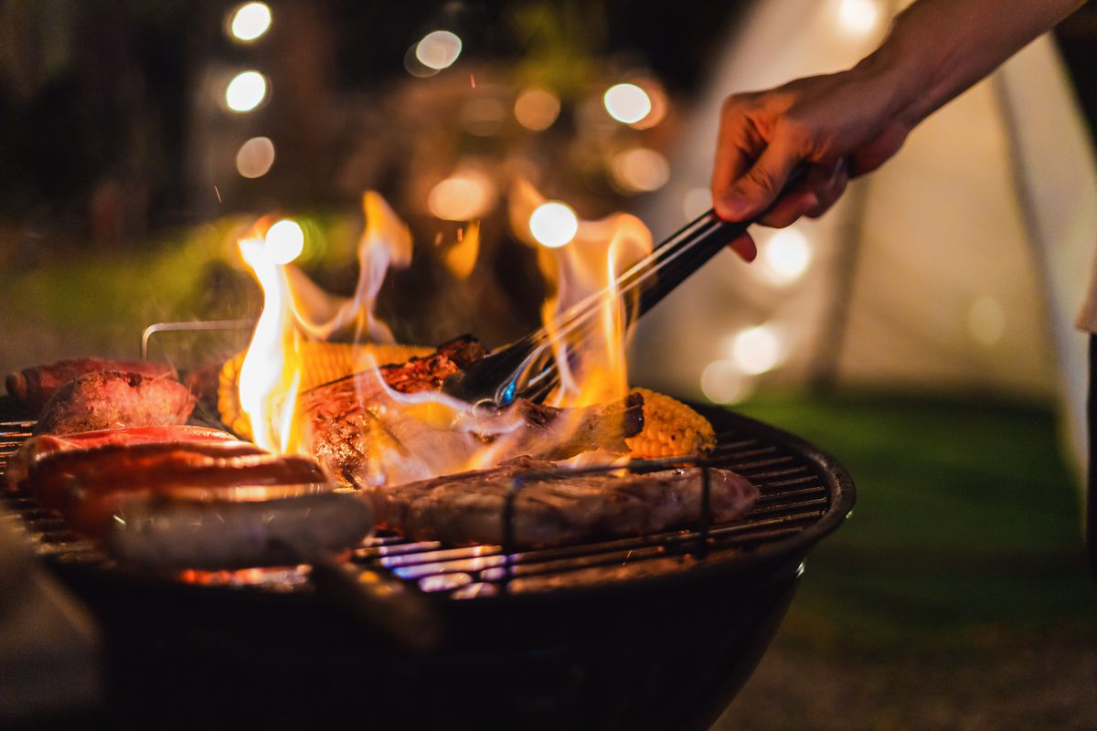A hand cooking food over a fired-up barbecue grill
