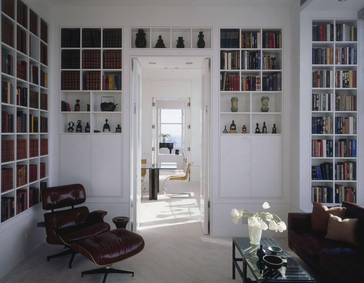 A white room with floor-to-ceiling built in book shelves. The shelves are filled with books, trinkets and encyclopedia sets. The room has a leather Eames recliner, a leather couch and a door that looks into a sunny room with a glass table.