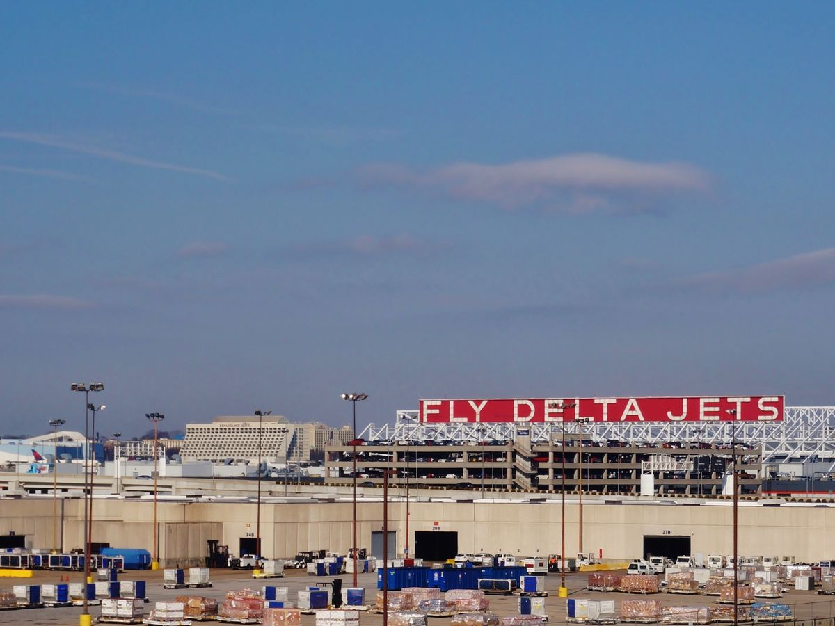 """Building with red and white """"Fly Delta Jets"""" sign on it."""