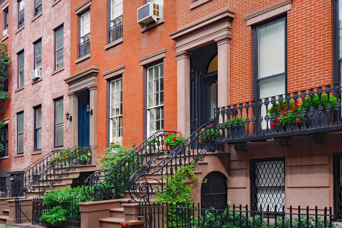 A brick home in NYC with pale pink trim, iron railings, and green shrubs.