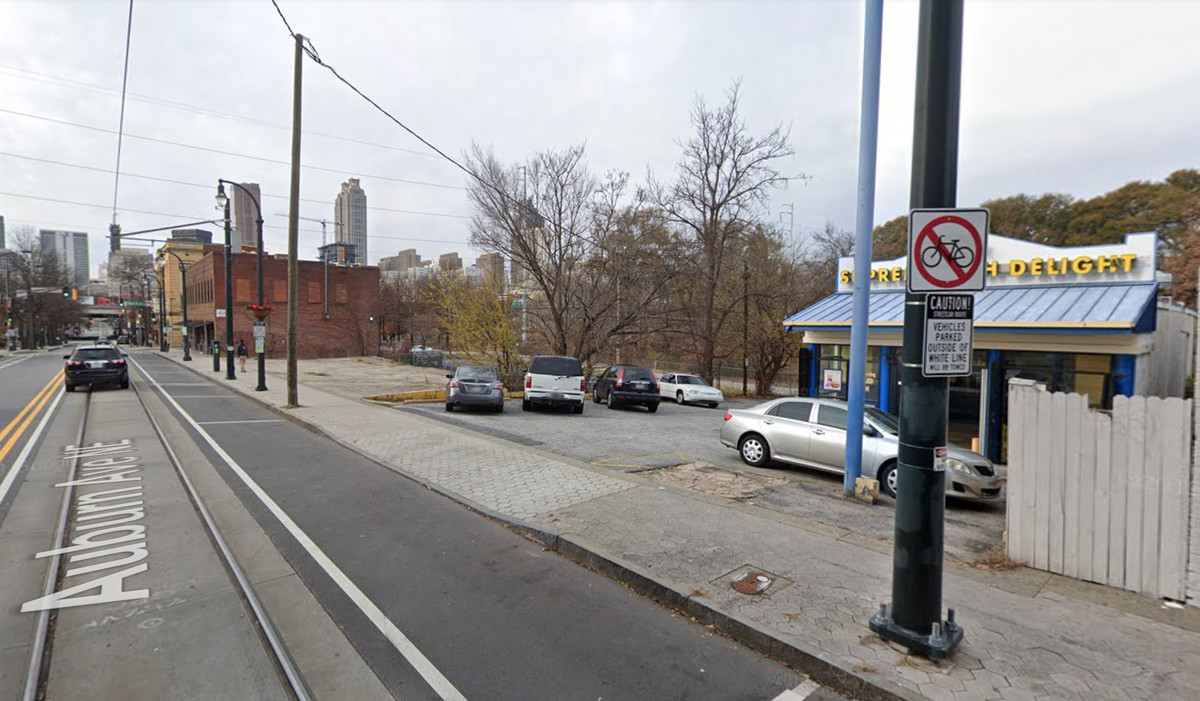 The streetcar track runs in front of a fish restaurant and empty lots.