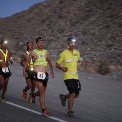 Oswaldo Lopez (L, #1) of Madera, California and Carlos Alberto of Portugal (C, #61) run wearing headlamp near Panamint Springs as night falls during the AdventurCORPS Badwater 135