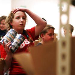 Caroline Crane, 14, sorts food with her family at the Utah Food Bank.