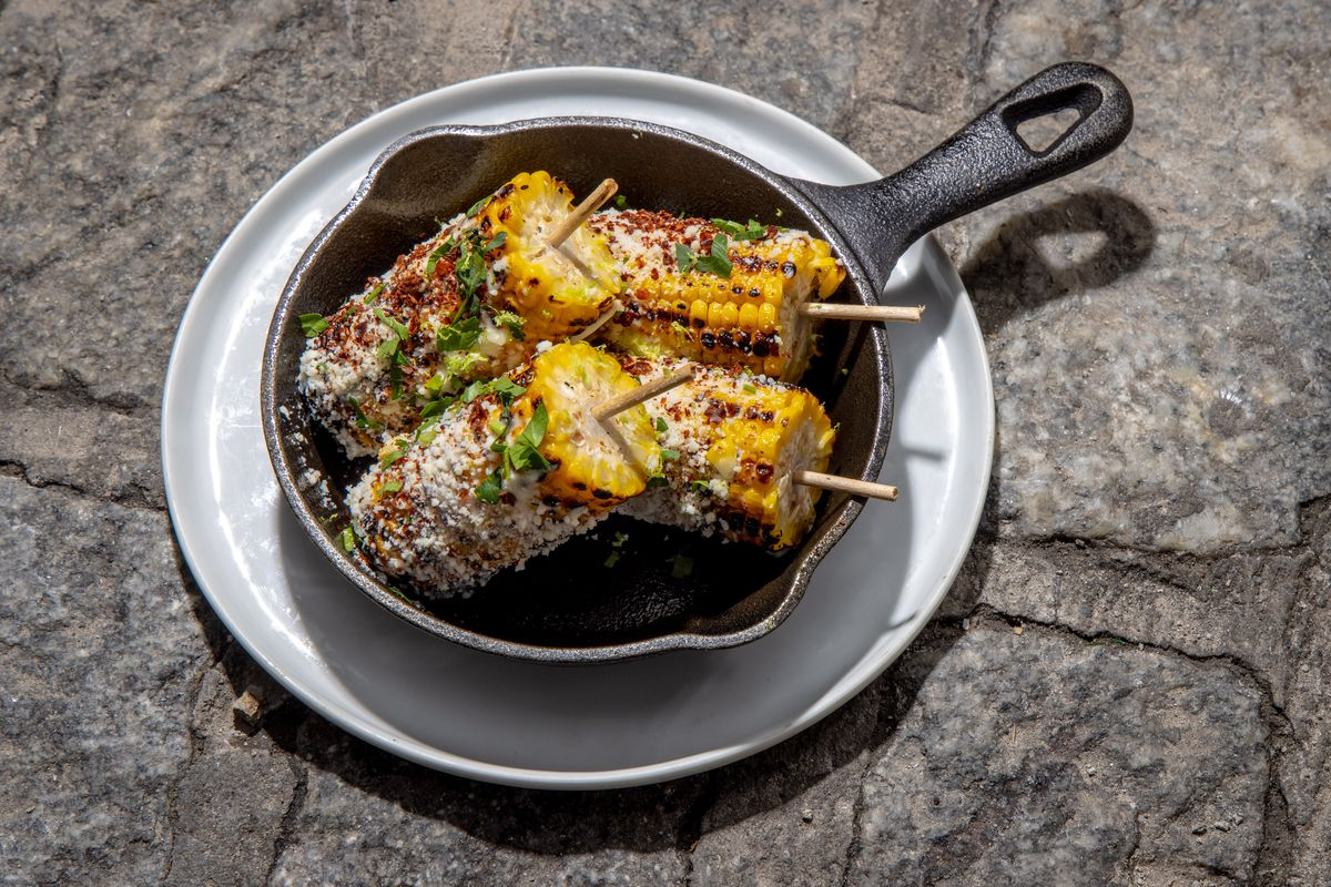 Four smoked, burnished mini-ears of corn sit in a cast iron skillet, covered in white cotija cheese and verdant cilantro
