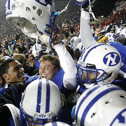 Brigham Young players celebrate their win over Utah at LaVell Edwards Stadium Saturday in Provo. BYU won in overtime, 26-23.