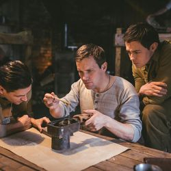 """From left: Callum McGowan, Jack Ashton and Elliot James Langridge act as prisoners of war Vinny Petrolini, Clair Cline and Reed """"Whit"""" Whitaker, helping Cline to make a violin by hand in the camp as seen in """"Instrument of War."""""""
