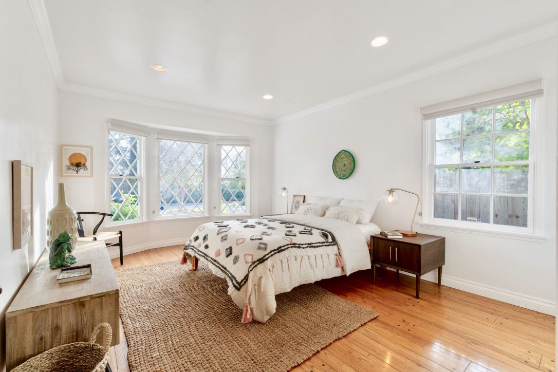 A room with two large windows and white walls. It's furnished with a bed, a night stand, and a dresser.