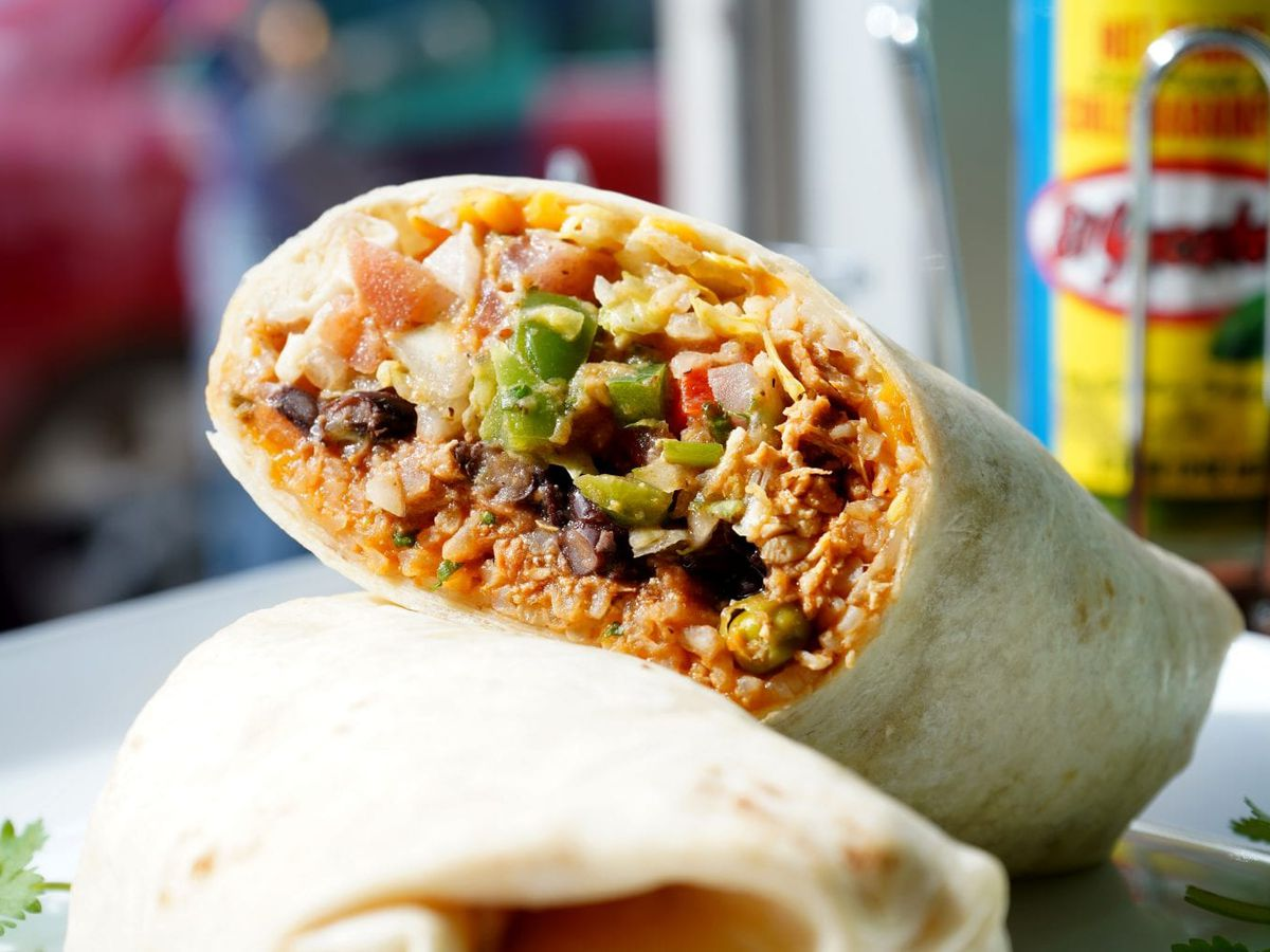Closeup of a burrito, with one half stacked on top of the other half. A bottle of hot sauce is visible in the background.