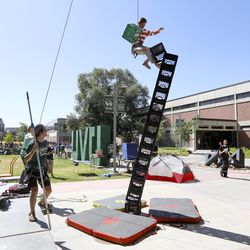Freshman Christian Williams falls from a stack of milk crates he had stacked at the Outdoor Adventure Center information booth at Utah Valley Universityin Orem campus on Wednesday, Aug. 28, 2019.